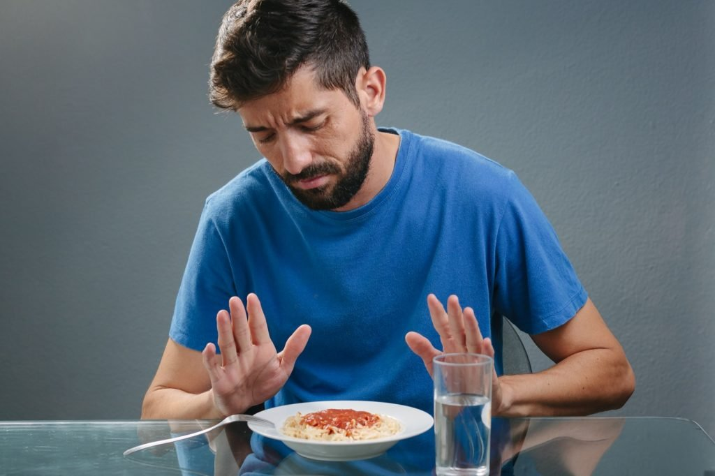 Man in blue colored shirt with no appetite in front of a meal