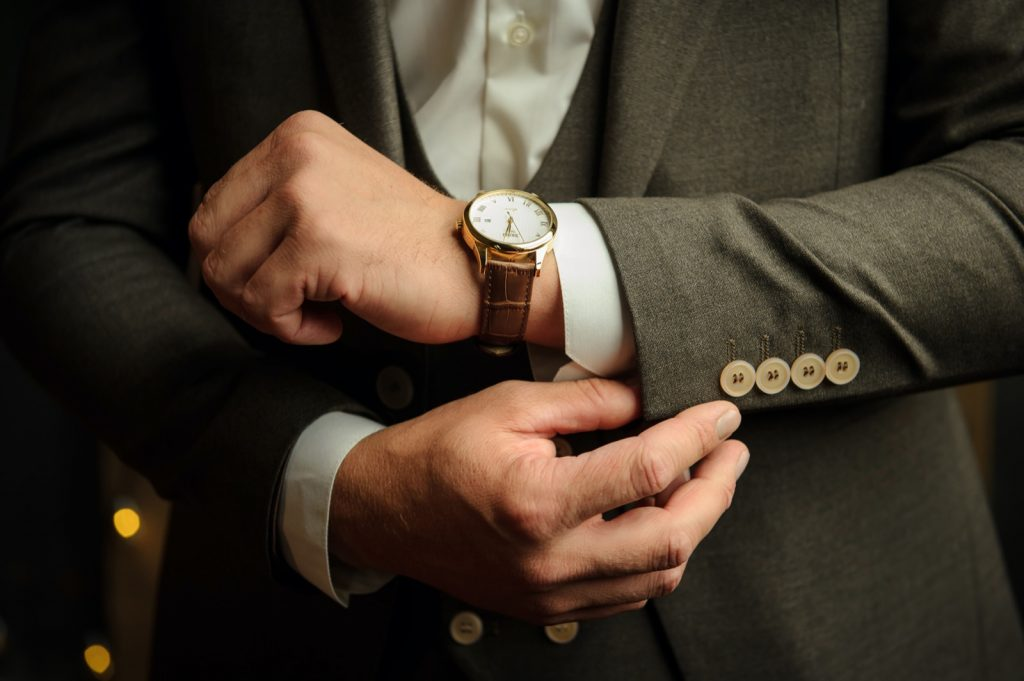 Man in gray suit wearing a luxury gold watch with a brown leather strap
