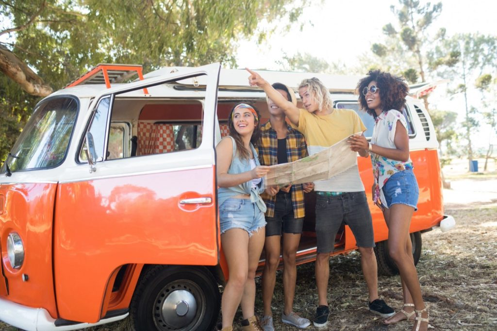 Man pointing and standing with friends near orange camper van