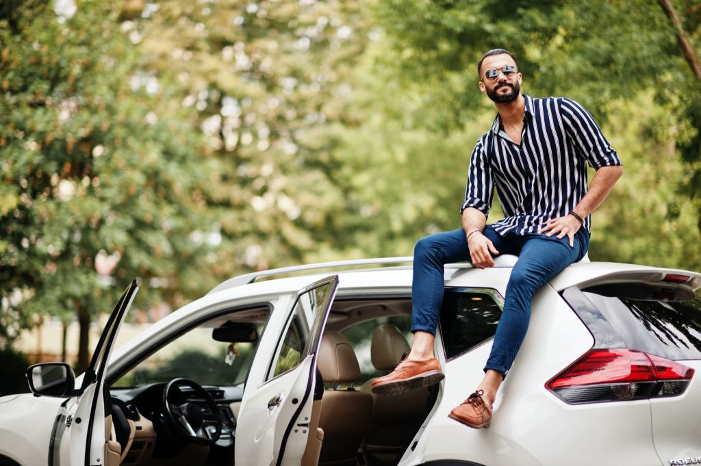 Man wearing striped shirt and sunglasses sitting on the roof of his white suv car