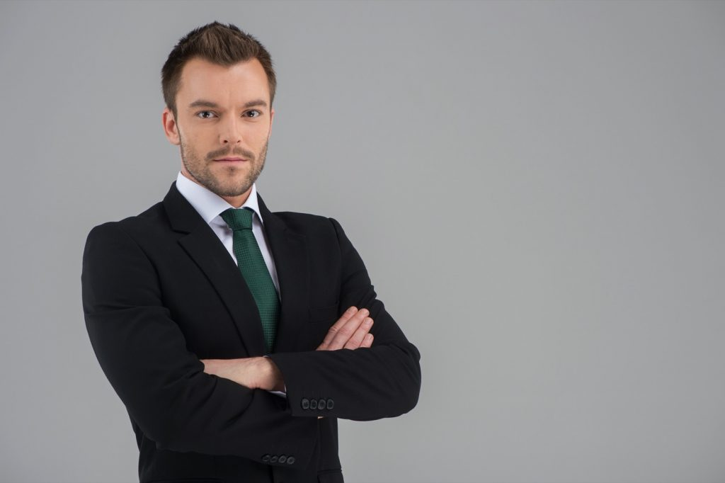 Man wearing a black suit and a green tie