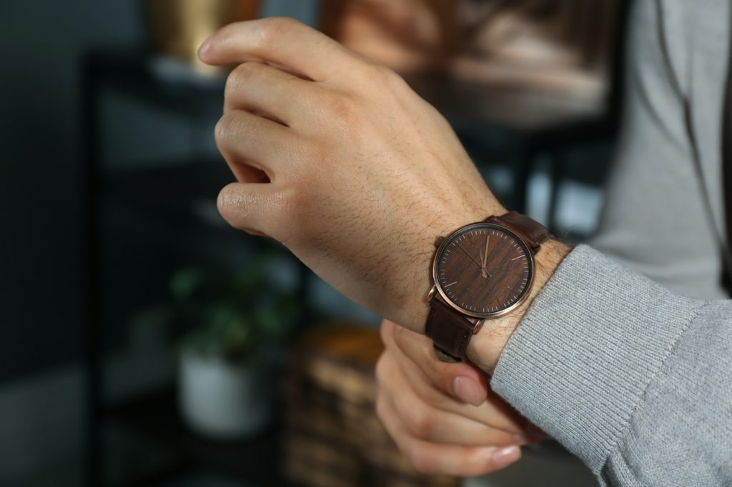 Man wearing brown wrist watch with wooden dial