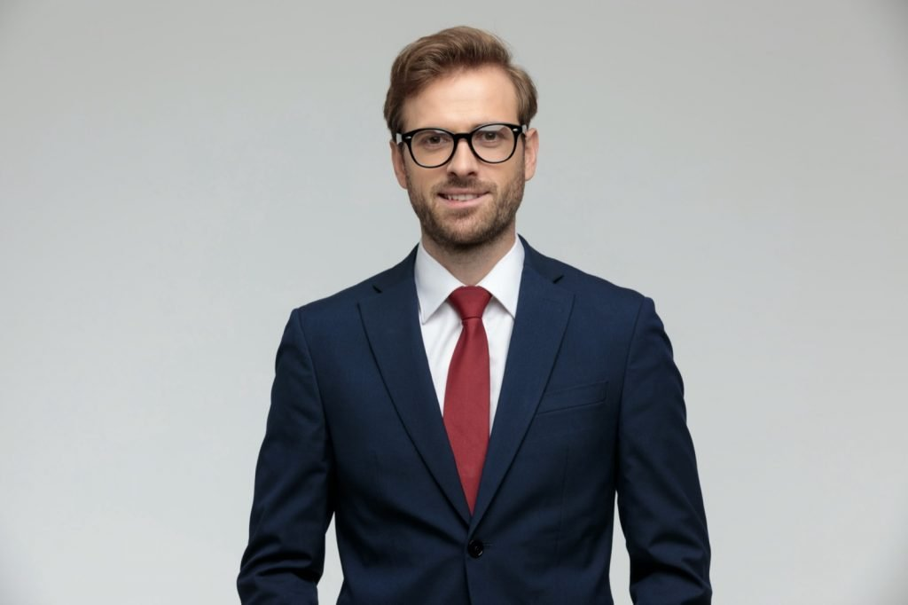 Man wearing suit, eyeglasses and red tie standing and looking at camera