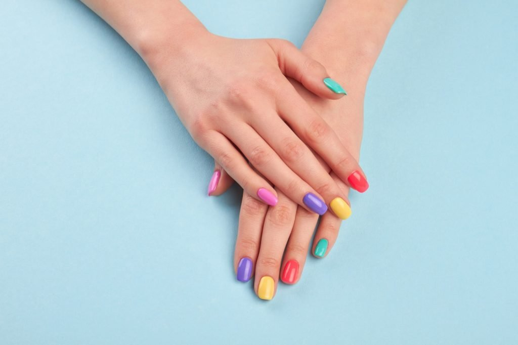 Manicured hands with stylish colorful nails on a light blue background