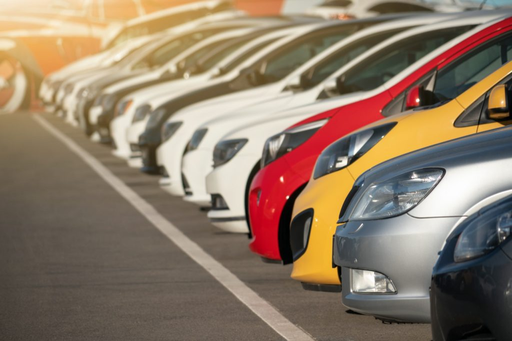 Many cars in different colors parked and lined up in a row
