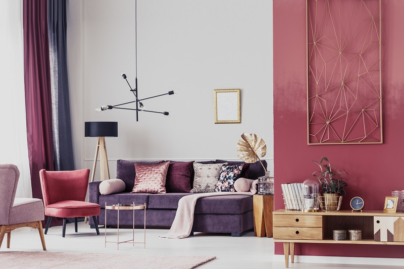 Red armchair next to a purple settee in cozy living room interior with wooden cupboard and lamp