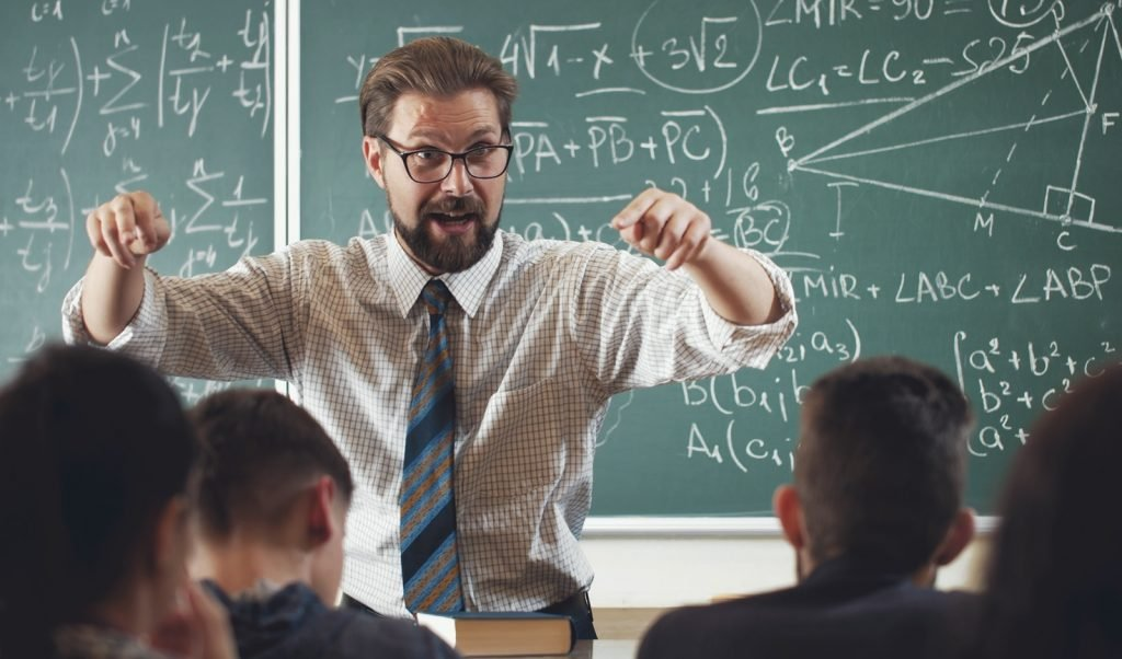 Enthusiastic math teacher explaining subject to students gesticulating with hands in school room