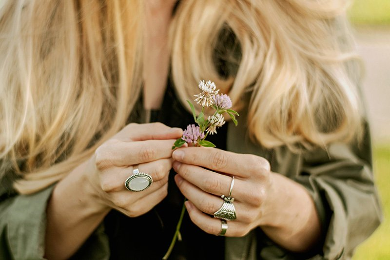 Woman with long blond hair holding flower in hand with mood ring on finger