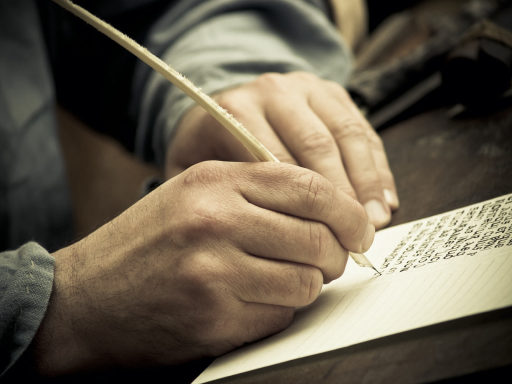 Medieval scribe writing on paper with feather pen