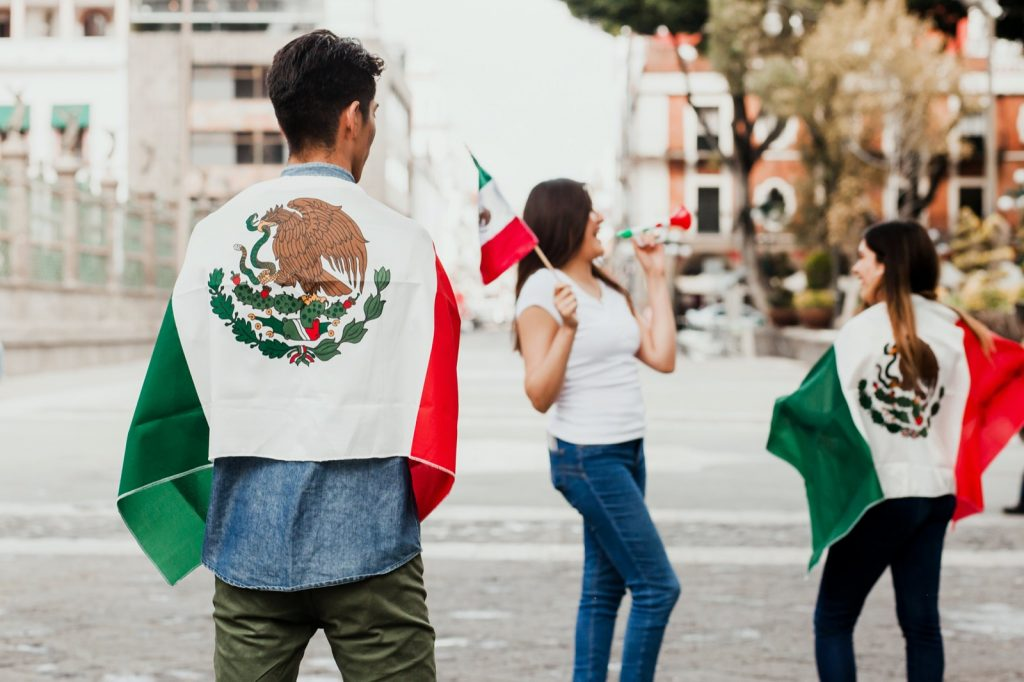 Mexican people cheering, wearing and holding the flag of Mexico