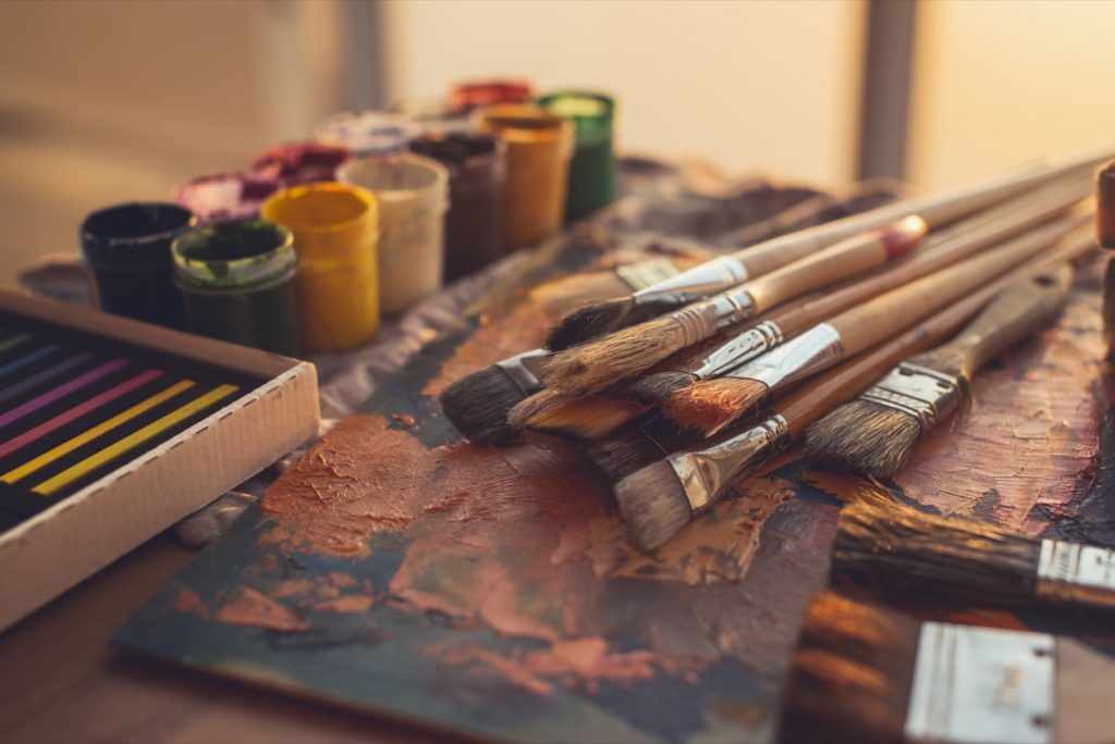 Angle view photo of color palette with mixed brown oil paints and paintbrushes