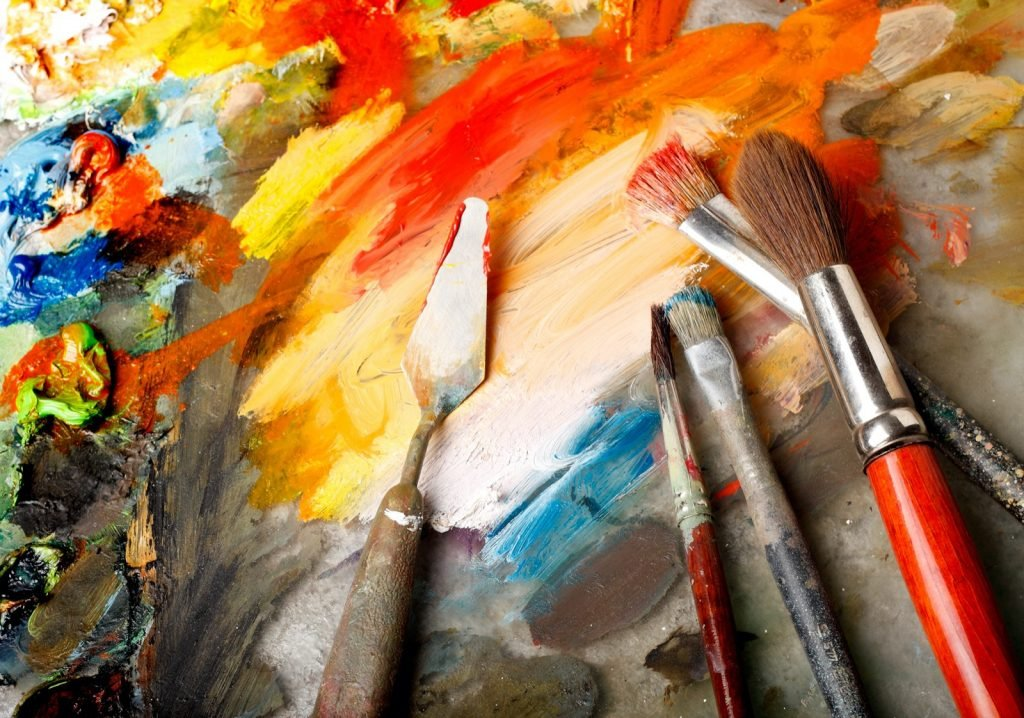 Paint brushes and palette with red, yellow and orange oil paints
