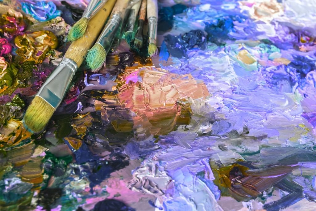 Artist palette with purple oil paints and brushes used for painting