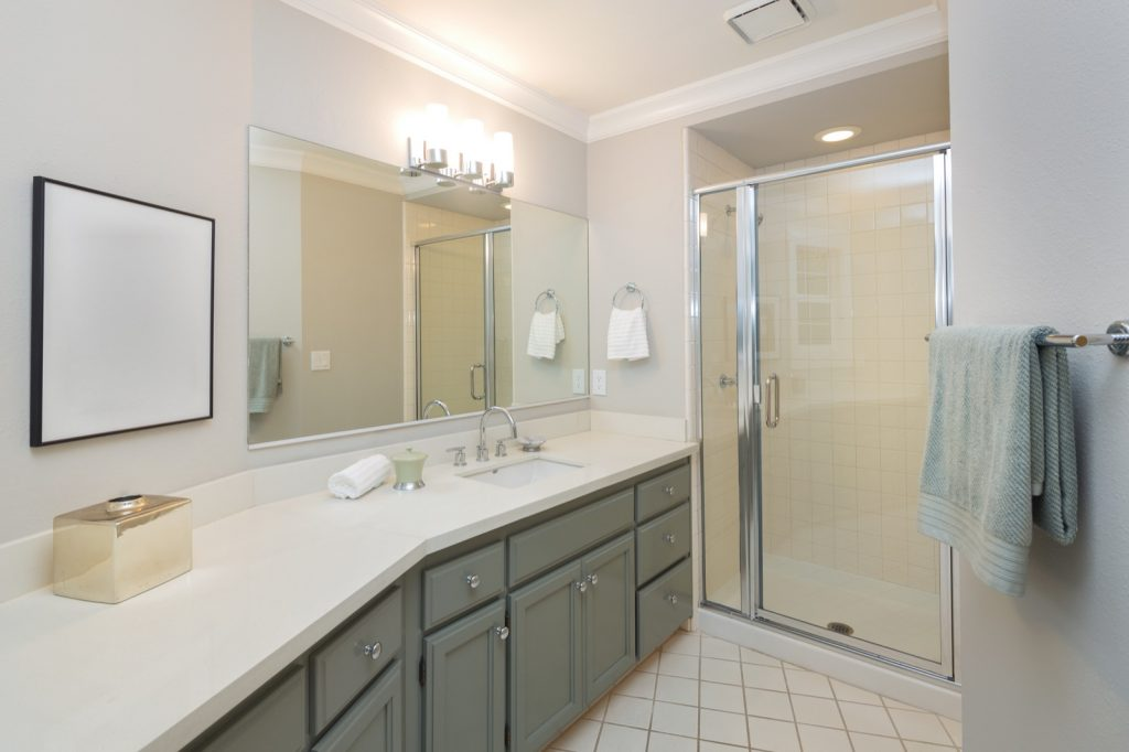 Modern bathroom with full bath shower, tile floor and vanity in green accent colors
