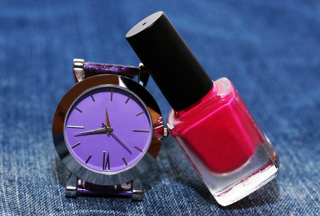 Modern purple wrist watch next to nail polish