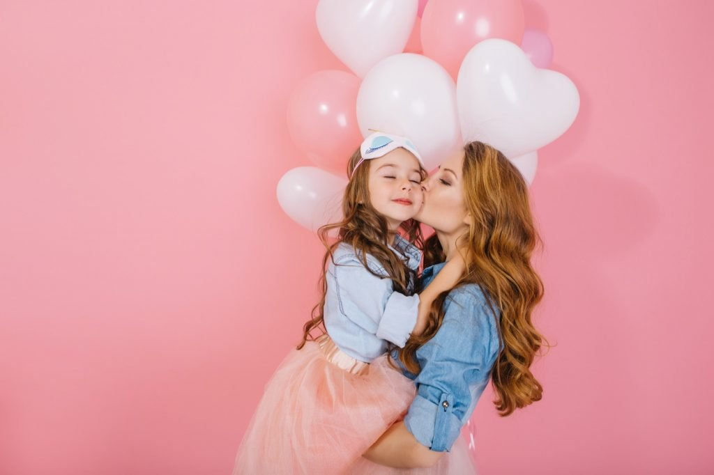 Mother and daughter on a pink feminine background
