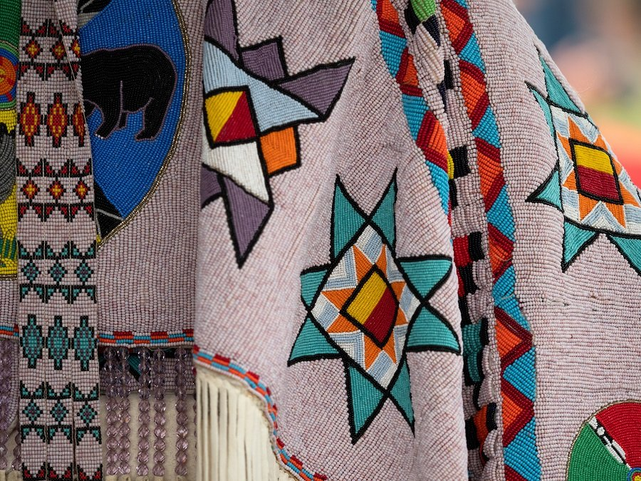 Beaded shawls and belts with geometric patterns and fringe worn at a pow wow.