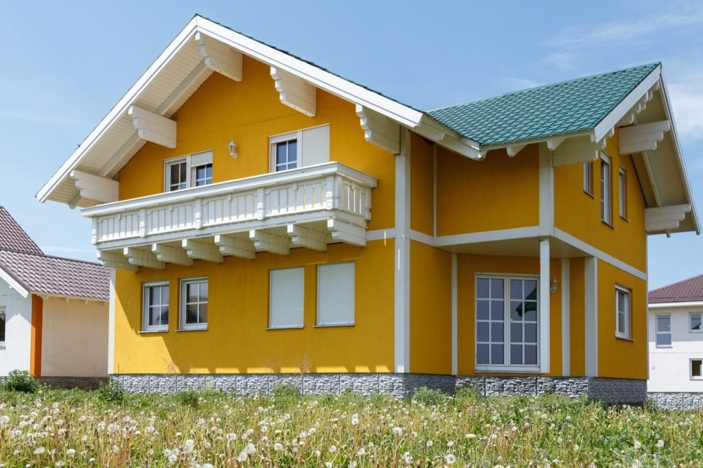 New yellow two-story house with white windows and a large wooden balcony
