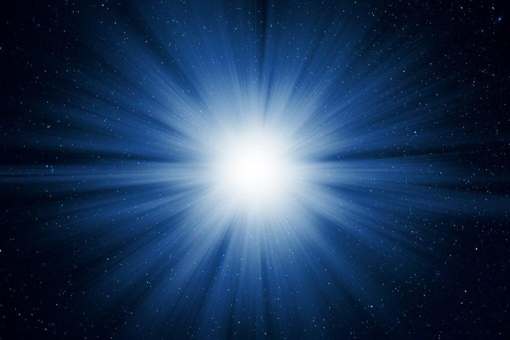 Starry night sky full of stars with white light burst explosion