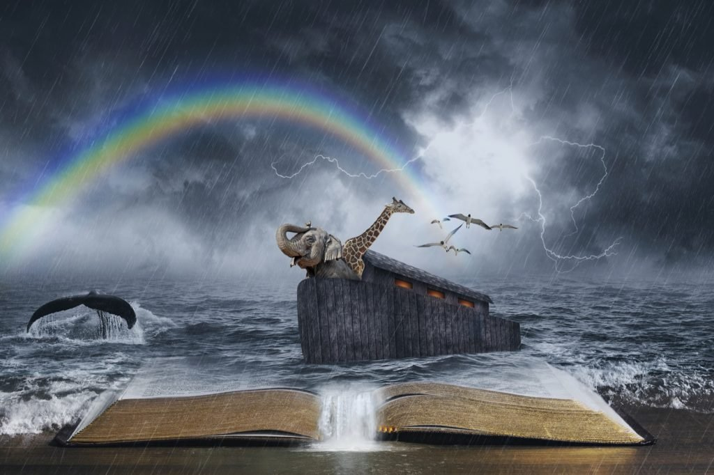 An open Bible with the story of Noah's ark and a colored rainbow