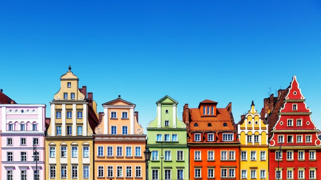 Old houses in different colors below a blue summer sky