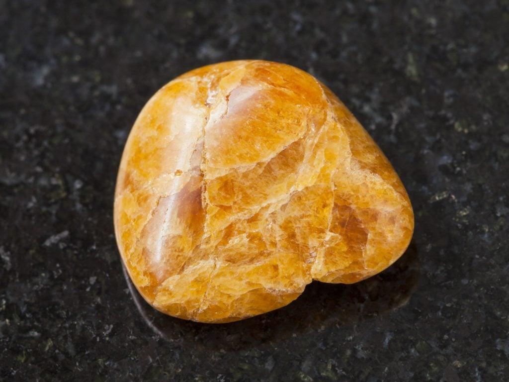 Closeup of orange Clinohumite gemstone on a dark granite background