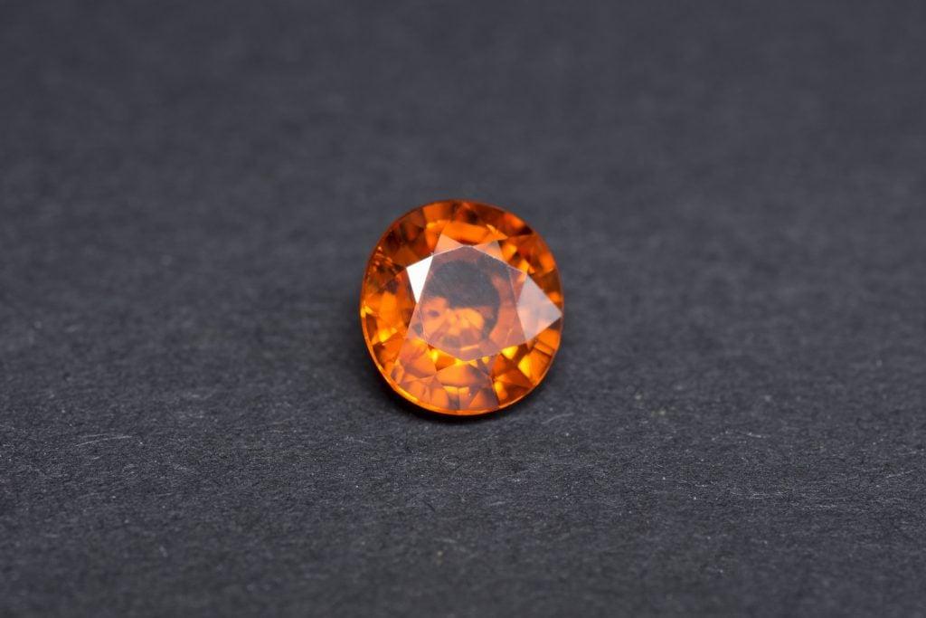 Cut orange garnet stone on a black background