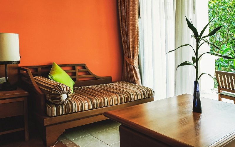 warm living room with orange walls and brown sofa