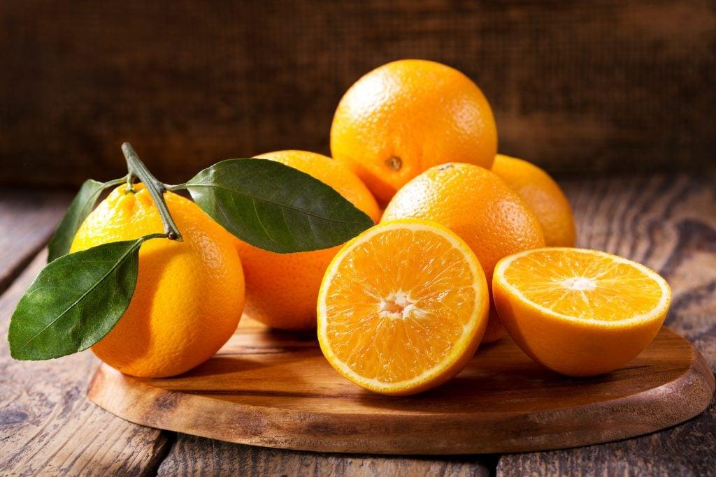 Fresh oranges on a dark wooden chopping board
