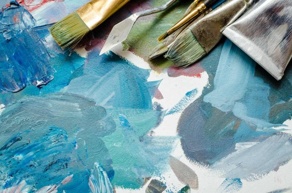Paint brushes and oil paint tube on artist palette. Mixed turquoise colors and other cyan shades
