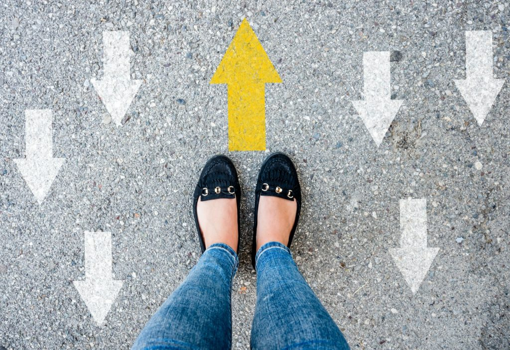 Paint your own path concept with yellow arrow in front of woman shoes and opposing direction arrows on asphalt