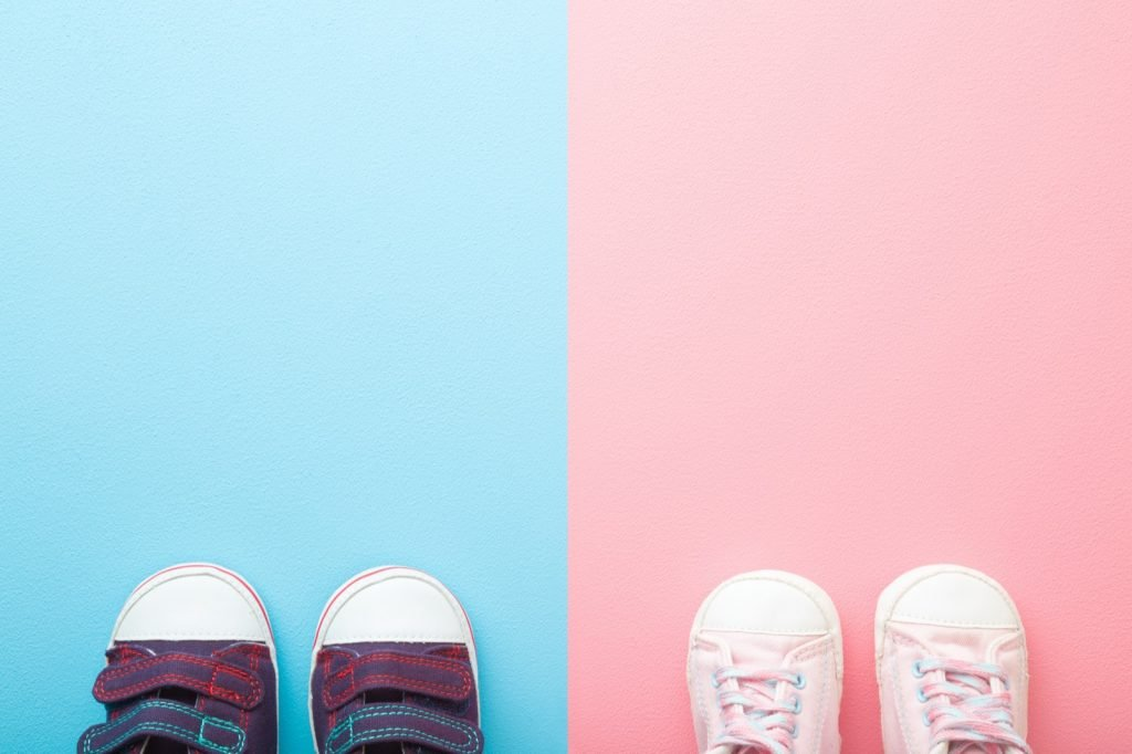 Pair of shoes on backgrounds with gender specific colors, blue for boys and pink for girls