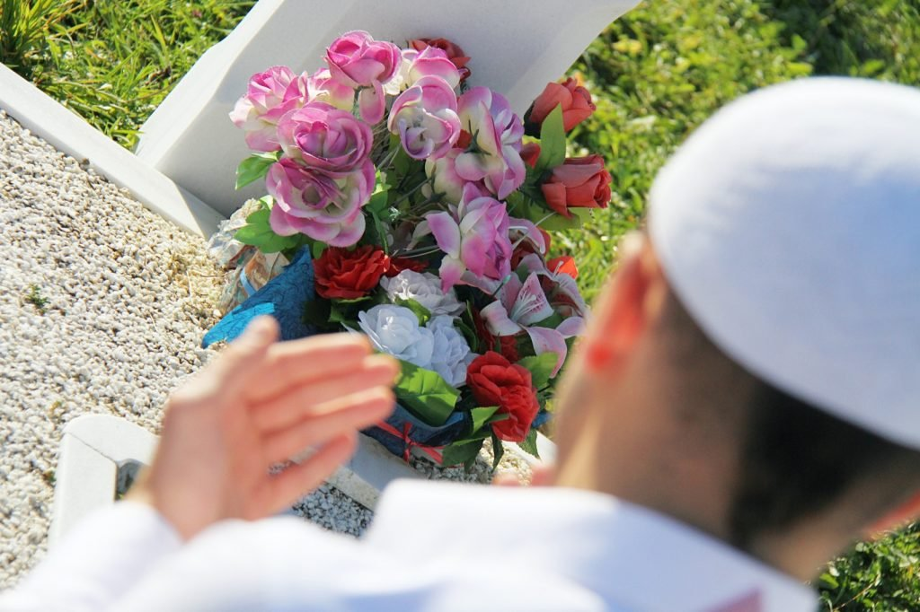 Pakistani man in white clothes praying in front of a gravestone