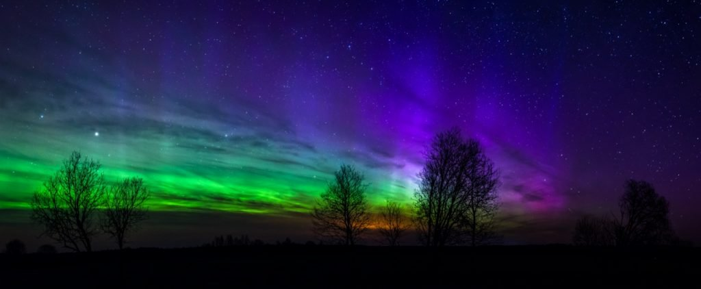 Panoramic photo of northern lights or aurora borealis in green, purple and orange colors