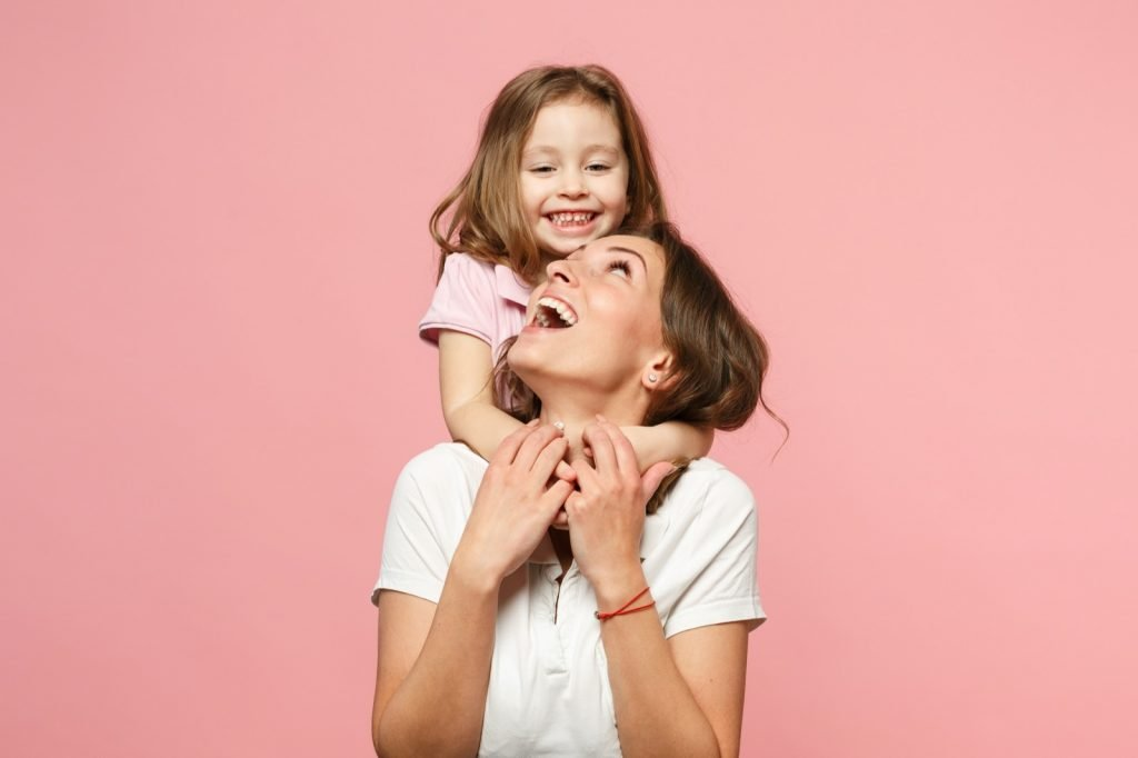 Portrait of mother in light clothes and daughter in pastel pink shirt isolated on pink wall background in a studio