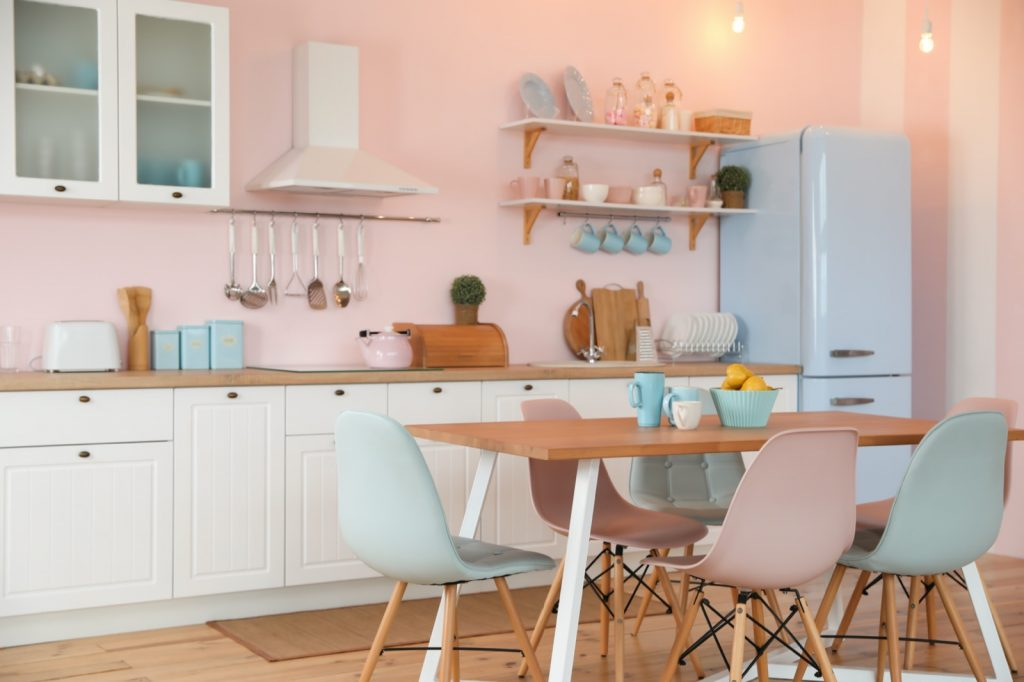 Pastel colored stylish kitchen interior with dining table and chairs