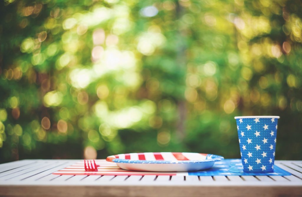 Patriotic party table setting outside with plate and cup in American flag colors