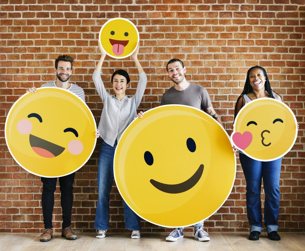 Group of people holding yellow emoji smiley faces
