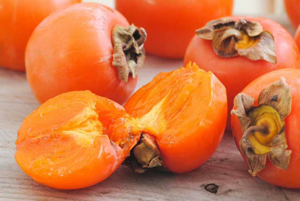 Closeup of fuyu persimmons fruits whole and one is cut in two pieces