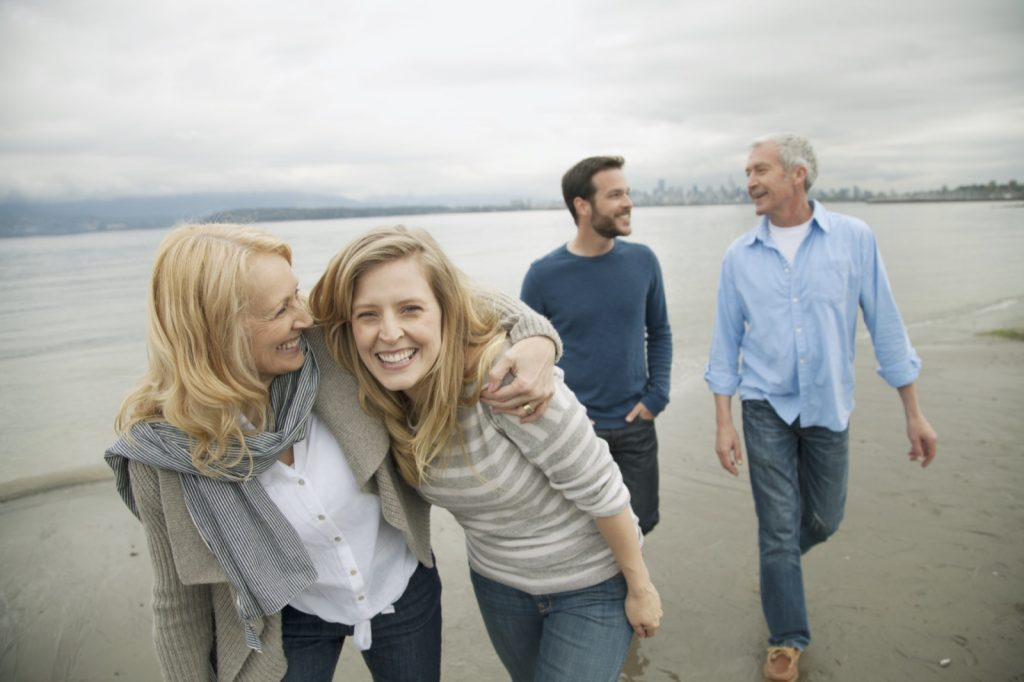 Photo of adult couple walking with parents on the beach