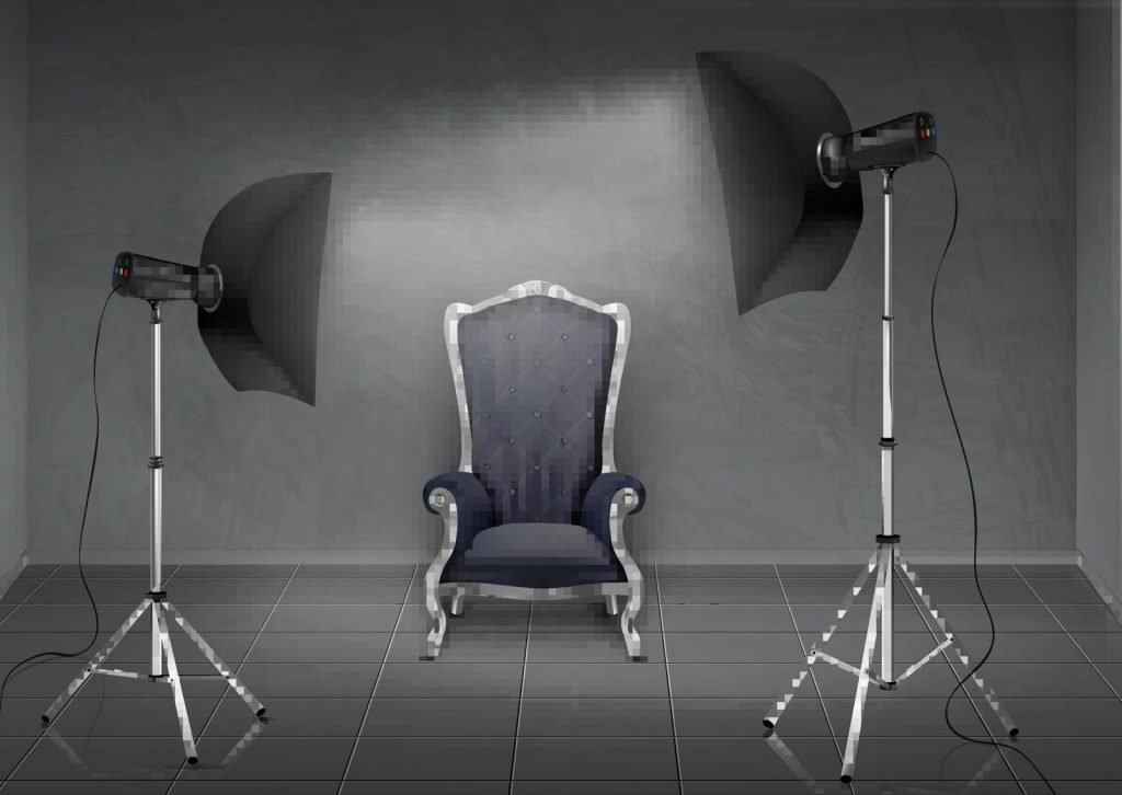 Professional photography studio with gray walls and floor. Empty armchair and lighting equipment on tripod stands