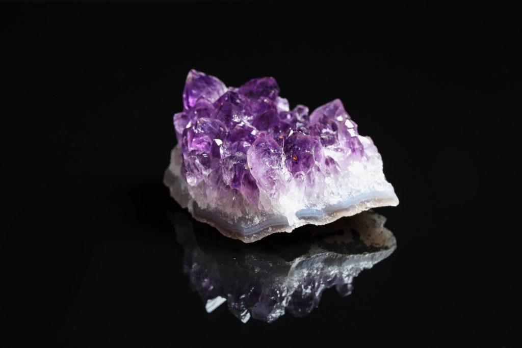 Piece of raw cut purple amethyst gemstone on black background
