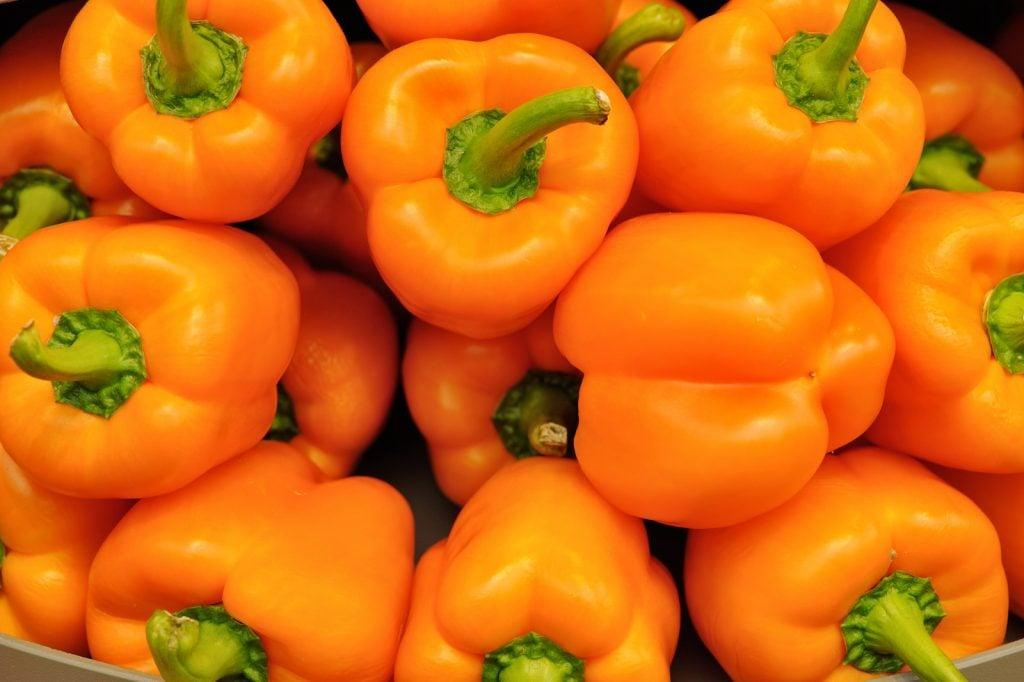 Closeup of big pile of orange bell peppers