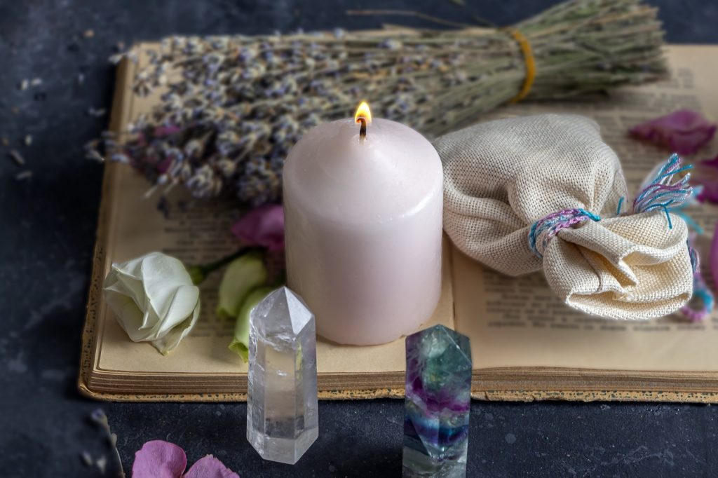 Pink candle and rocks for magic ritual in witchcraft, Wiccan or spiritual practice