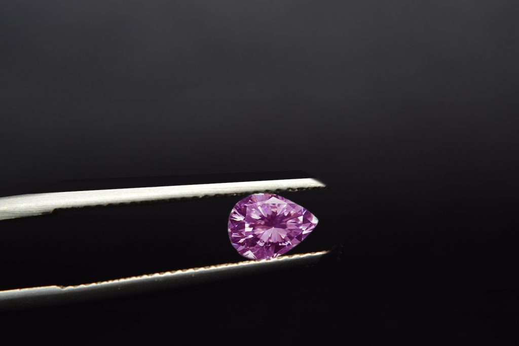 Close up of small pear shaped pink diamond being hold by a tweezer against a black background