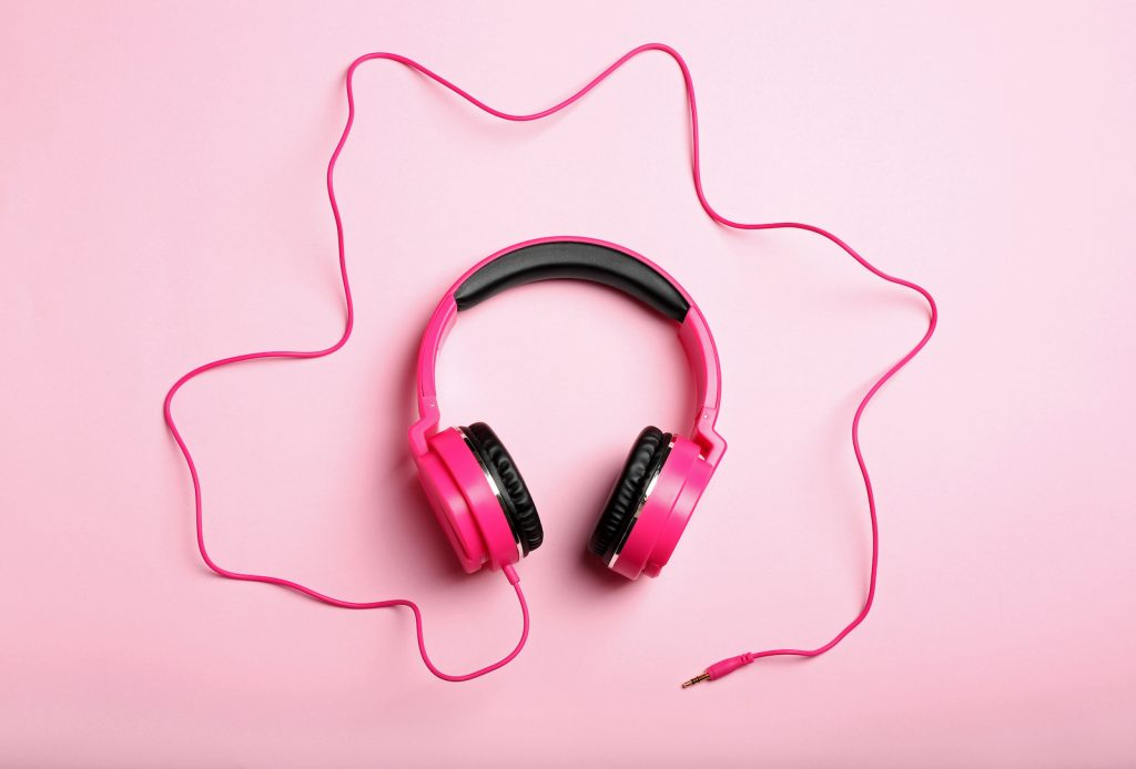 Dark pink headphones lying on a softer pink background, waiting for someone to hear pink noise