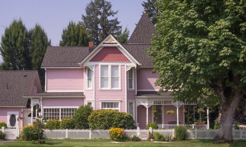Pink Victorian house with a white picket fence and a big maple tree