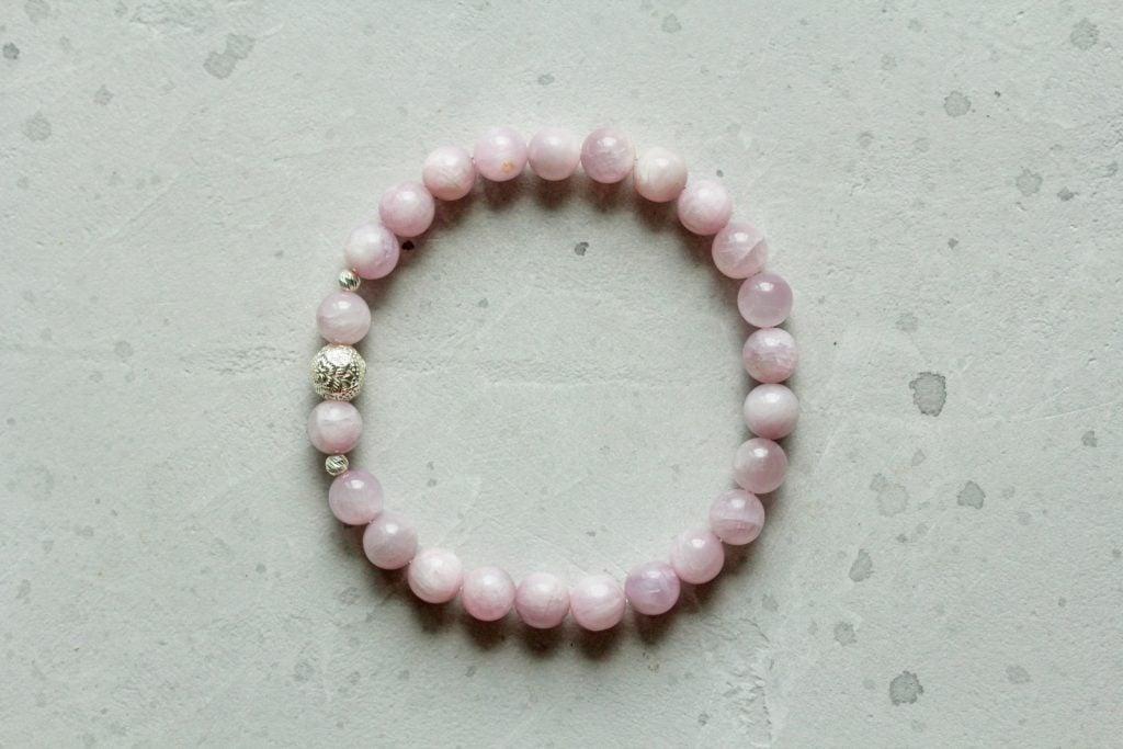 Pink kunzite bracelet lying on a concrete surface
