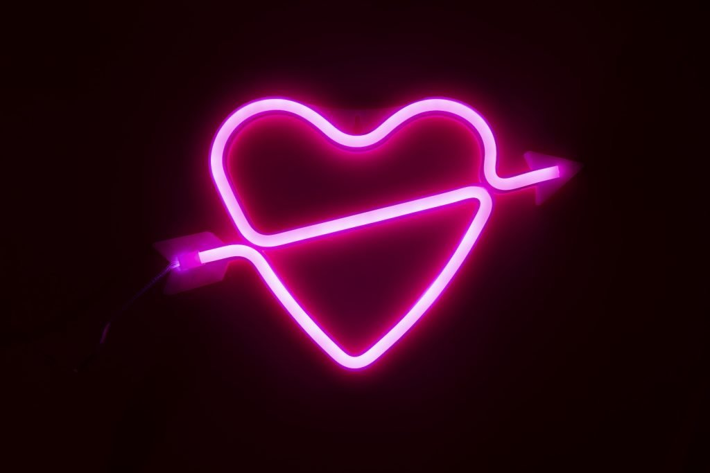 Pink glowing neon light heart with an arrow