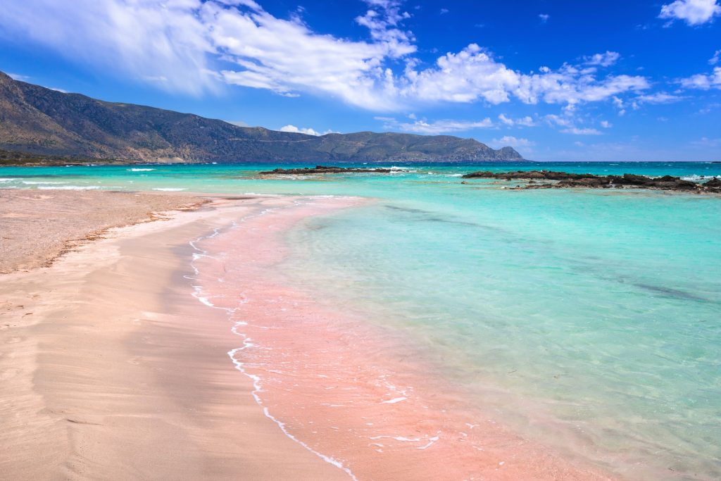 picture of a beach with pink sand and the cleare blue sea